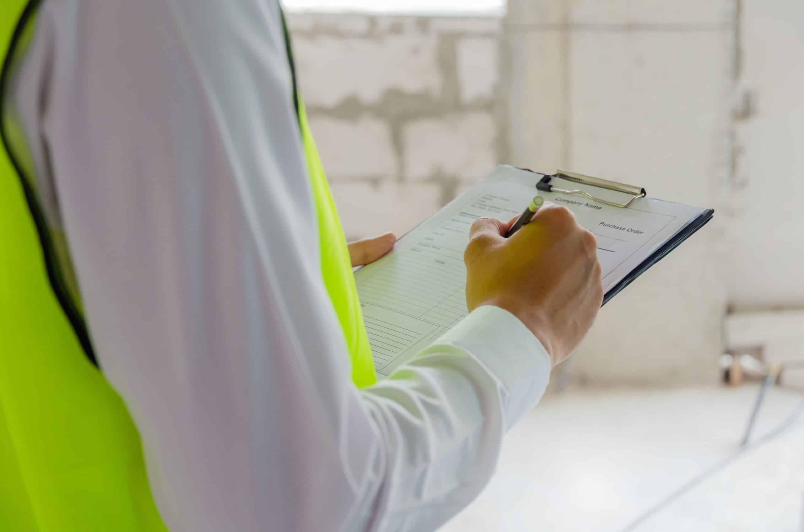 Man maakt notities in checklist tijdens werkplekinspecties